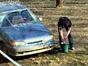 моет машину в парке