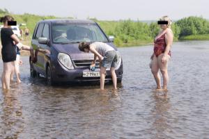 моет автомобиль на речке