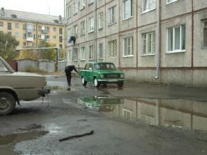 моет машину во дворе
